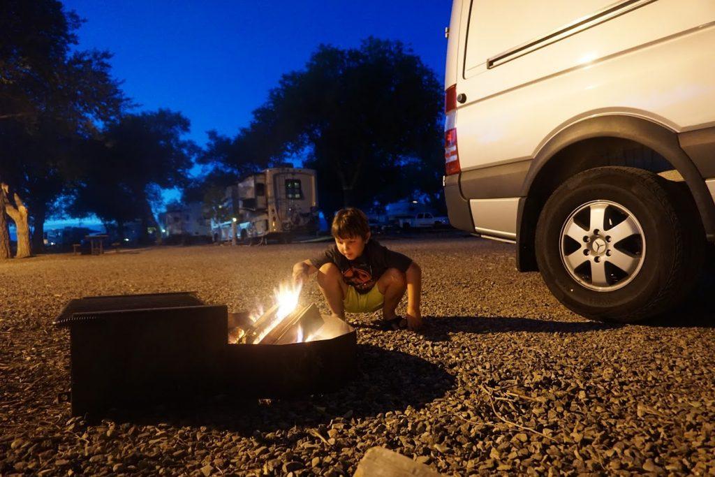Jack at campfire outside of Sprinter conversion camper van.